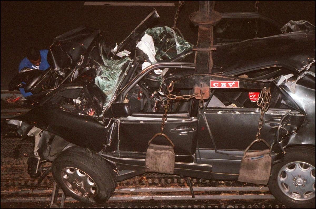 A French policeman attaches the wreckage of Princess Diana's car 31 August in the Alma tunnel of Paris.