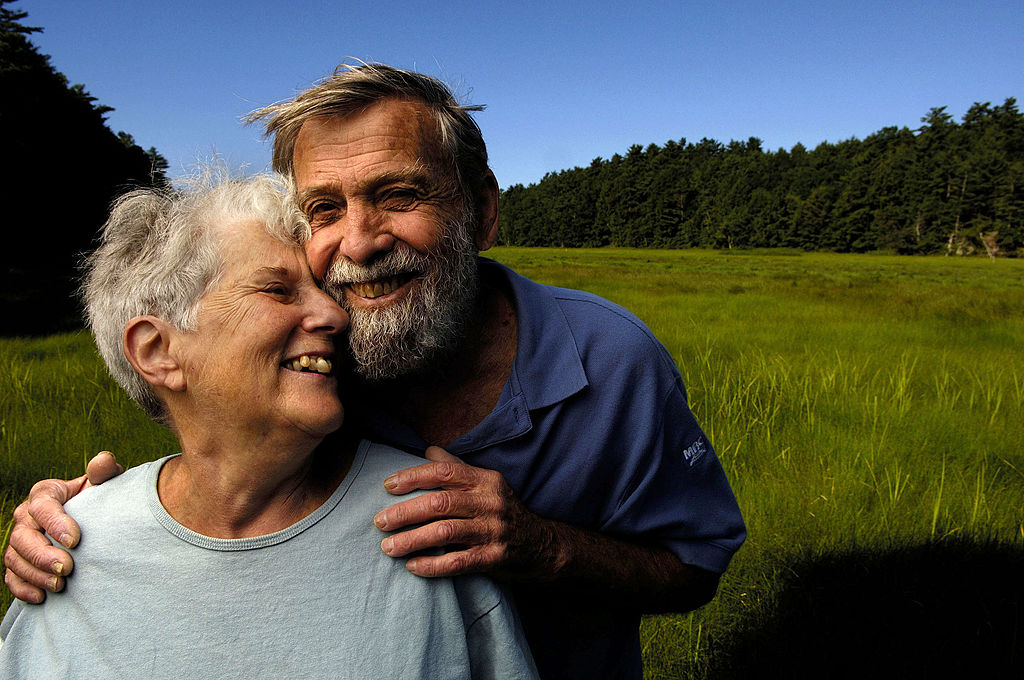 An elderly couple smiles and pose close together.