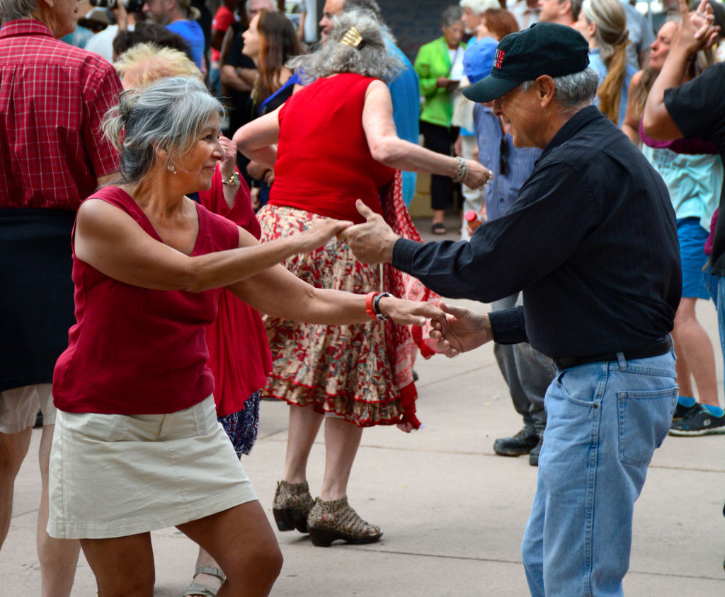A retired couple dancing outside amongst a crowd.