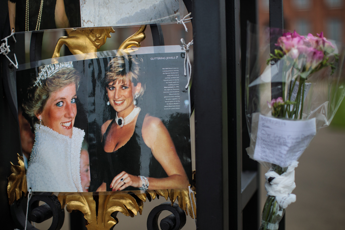 Floral tributes, photographs and messages sit on an entrance gate to Kensington Palace honor the 20th anniversary of the death of Diana.
