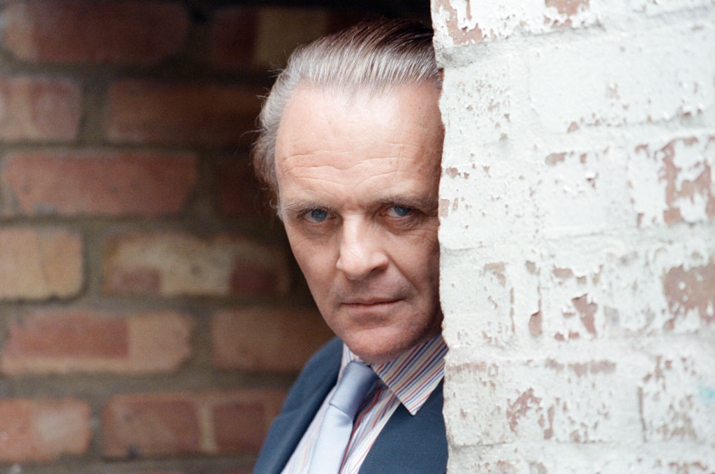 Anthony Hopkins looks grim while peeking from behind a brick wall.