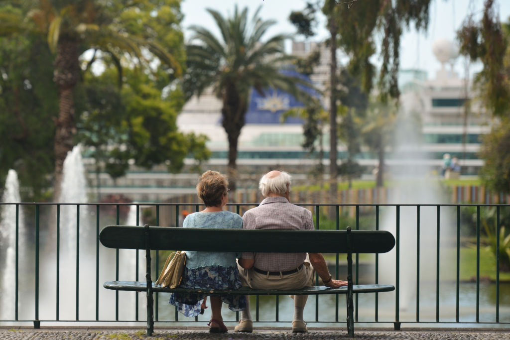 A elderly couple sits on a bench near a lake.