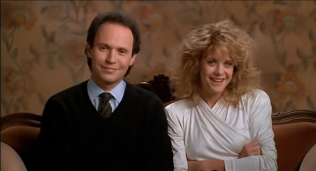 Harry and Sally sit on a coach smiling while being interviewed.