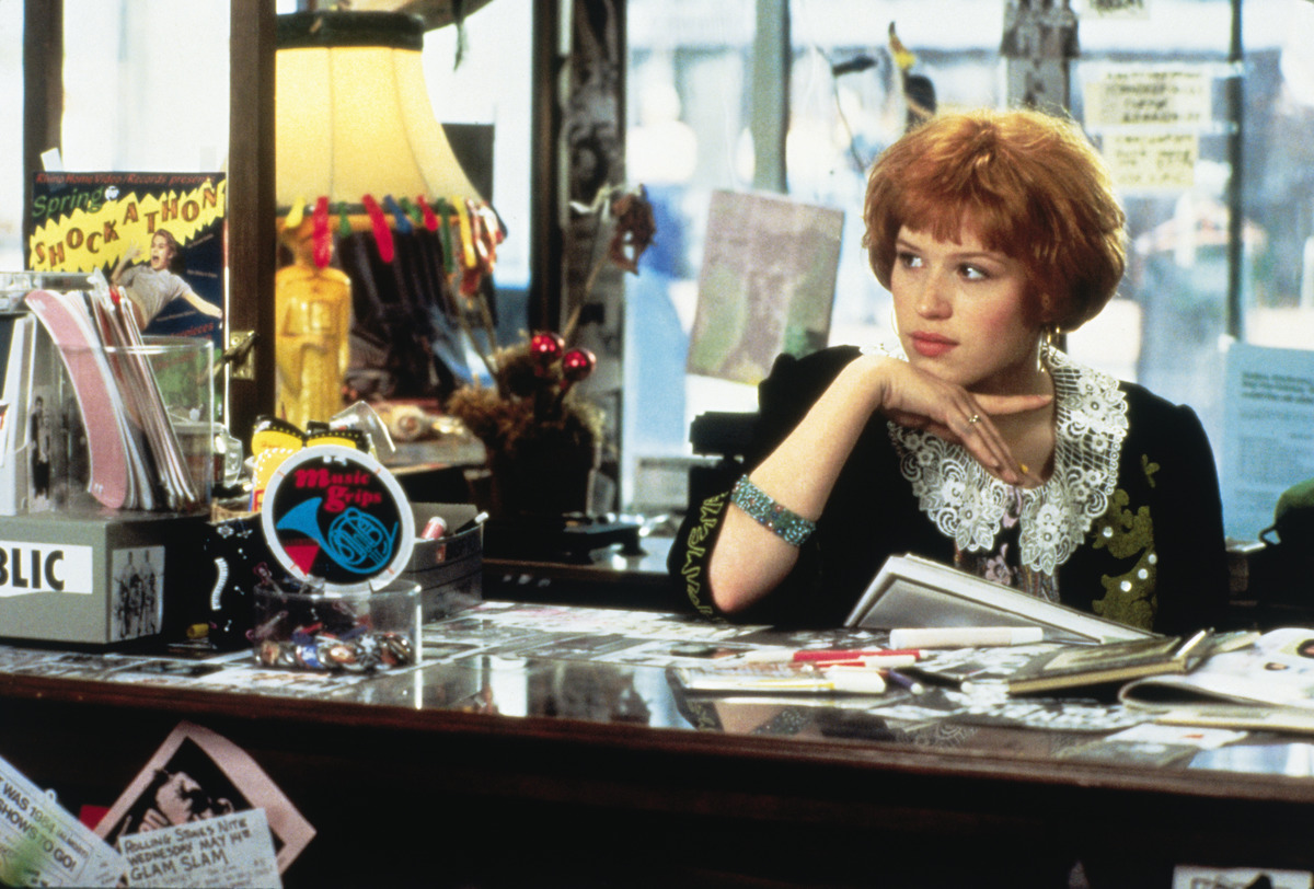 Molly Ringwald sits at a store counter in Pretty In Pink.