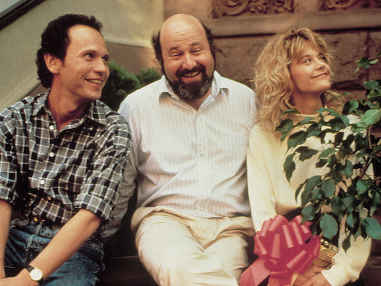 Rob Reiner sits and smiles with his leads.