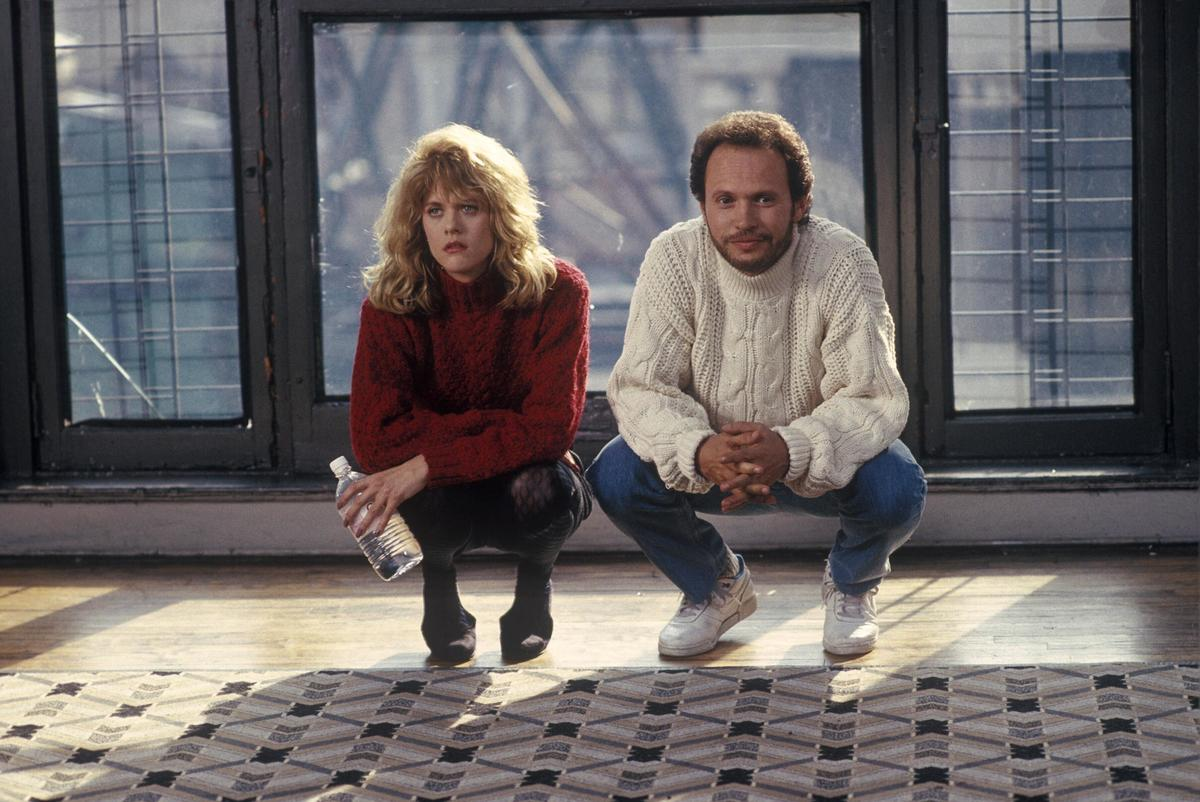 Harry and Sally squat down next to one another in front of a window.