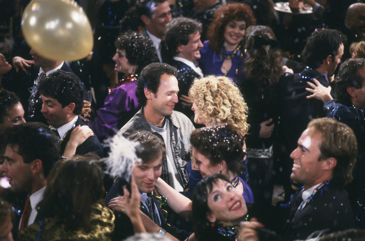 Harry and Sally smile at one another in the middle of a crowd on New Year's Eve.
