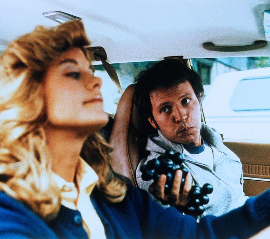 Harry offers Sally some grapes while she drives.