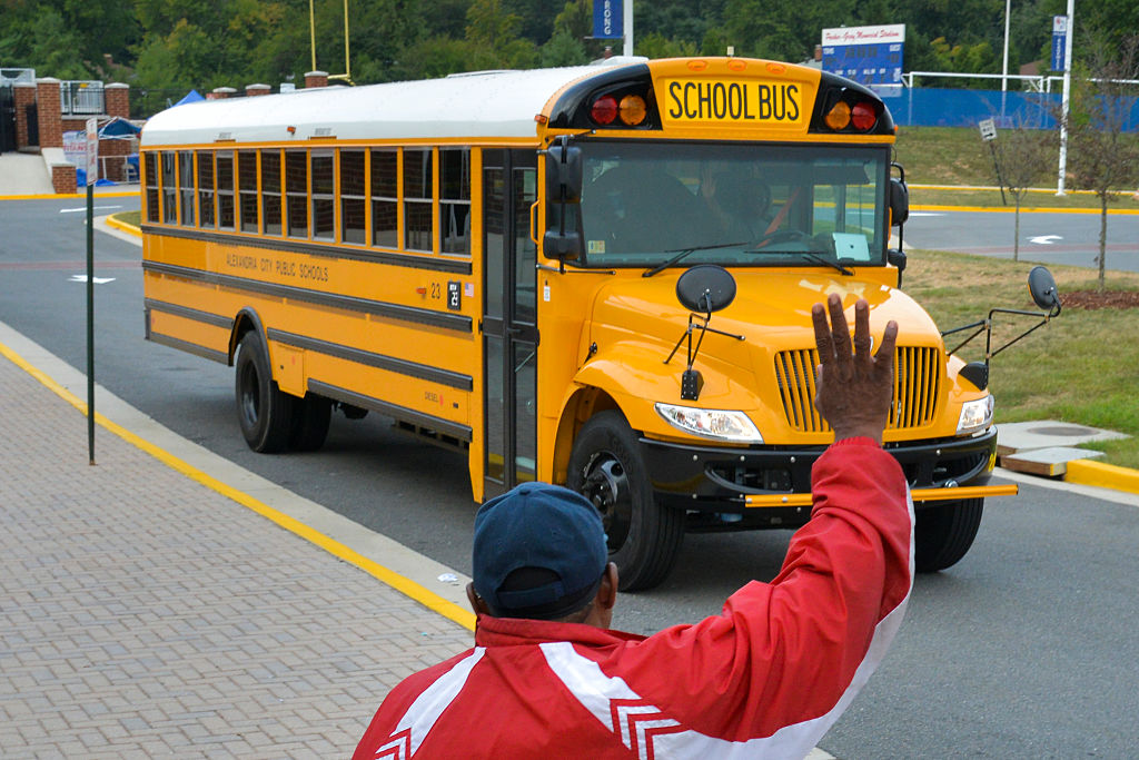 a parent waving to a school bus