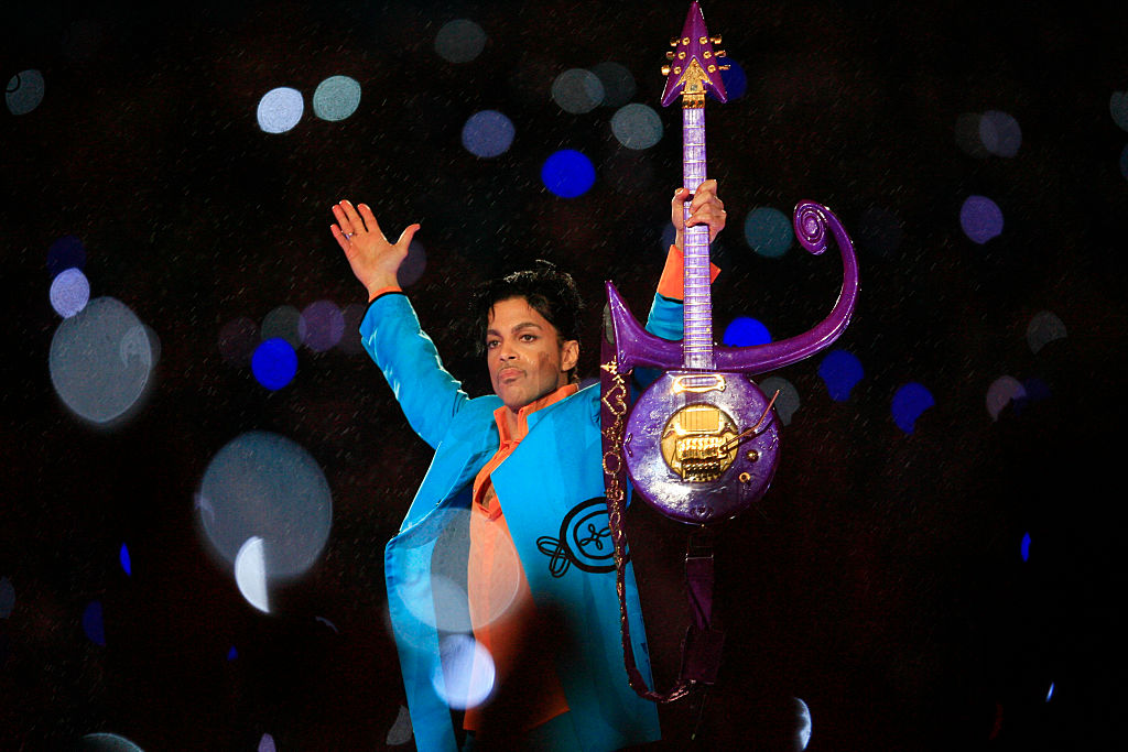 Prince raises his arms and his guitar while performing at the Super Bowl.