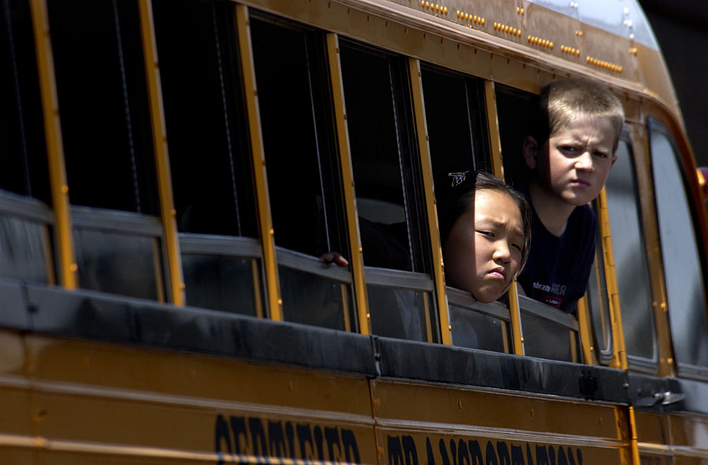 kids sticking their heads out of the school bus
