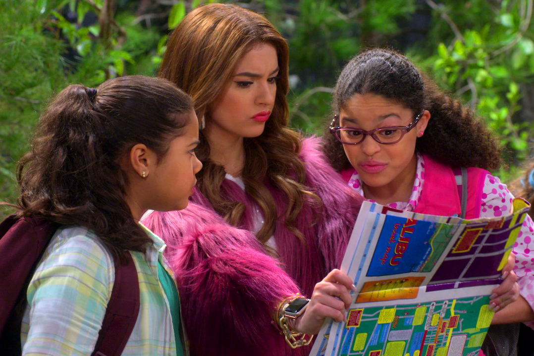 A screenshot of the show Team Kaylie shows Kaylie looking over a wilderness map with students.
