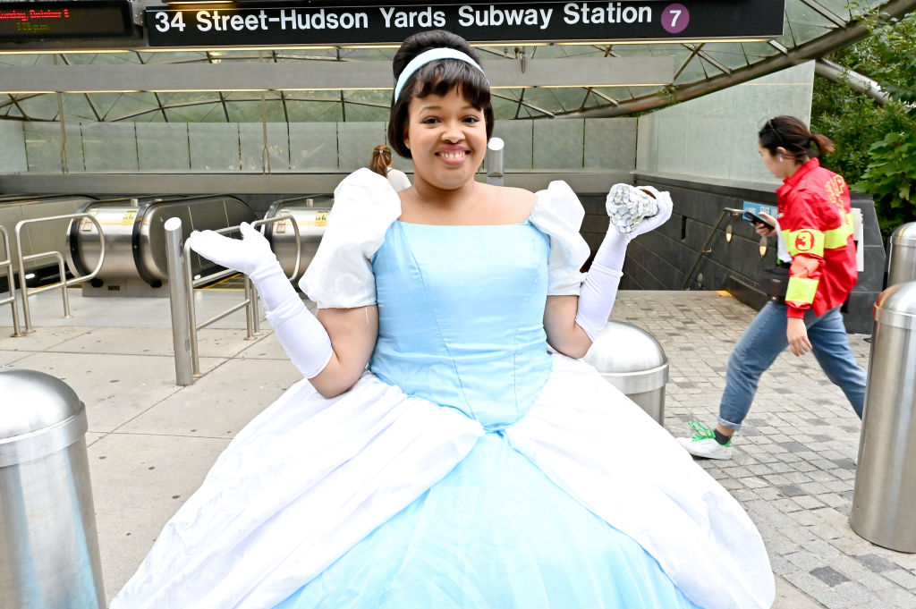 a woman outside a subway station dressed as cinderella