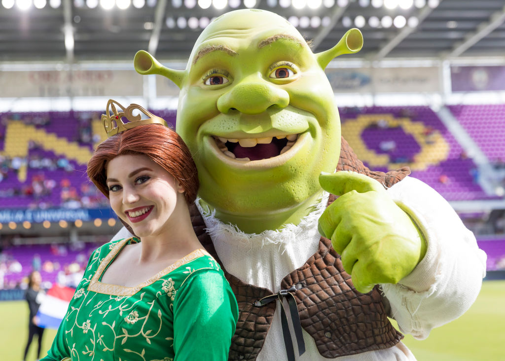 a woman dressed as fiona with a shrek mascot on a soccer field