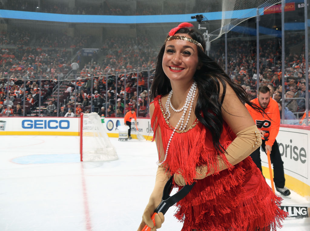 a woman dressed as a flapper at an ice hockey game
