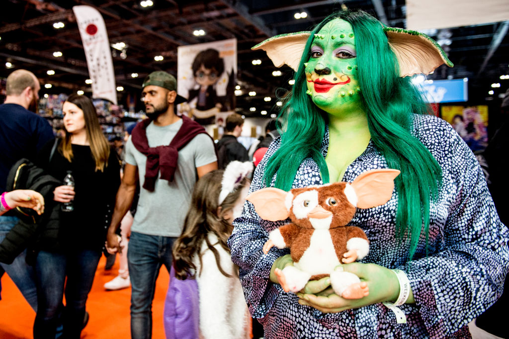 a woman dressed as a gremlin holding a stuffed animal from gremlins