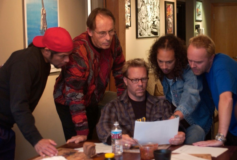 The band members of Metallica reconvene and look at a paper.
