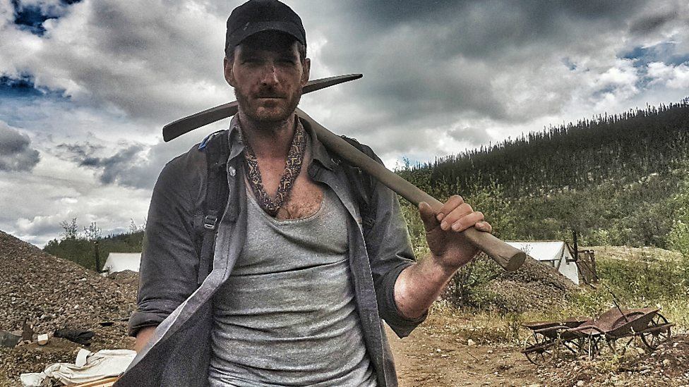 Dan Snow carries a pick axe through Canada in the show Operation Gold Rush.