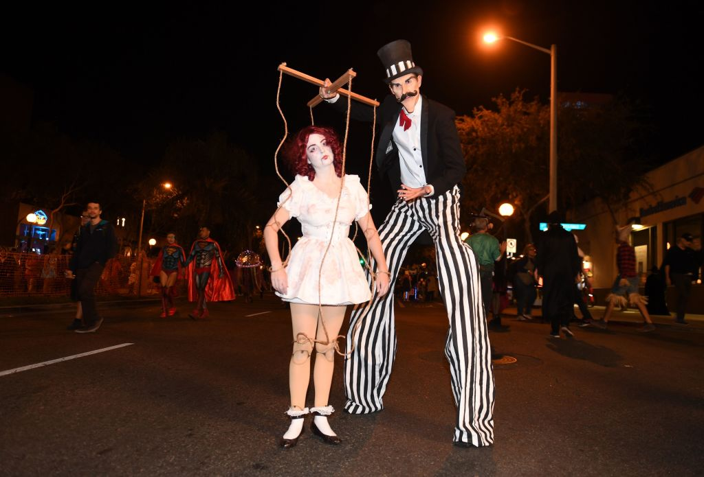 a woman dressed as a puppet next to a guy in stilts