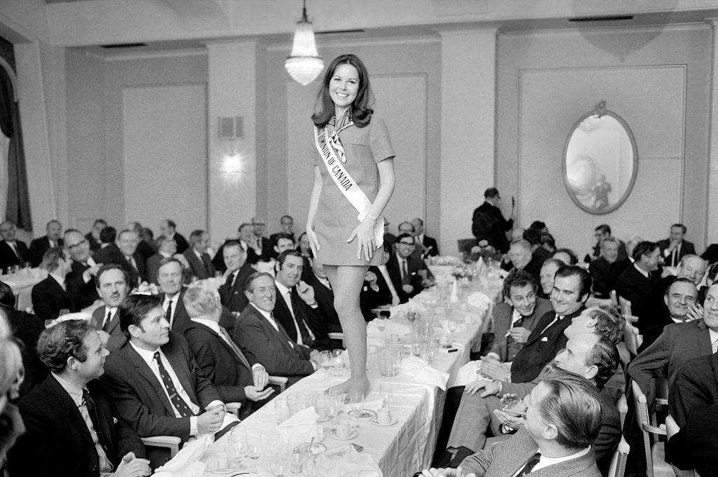 a beauty pageant winner standing barefoot on a table filled with men