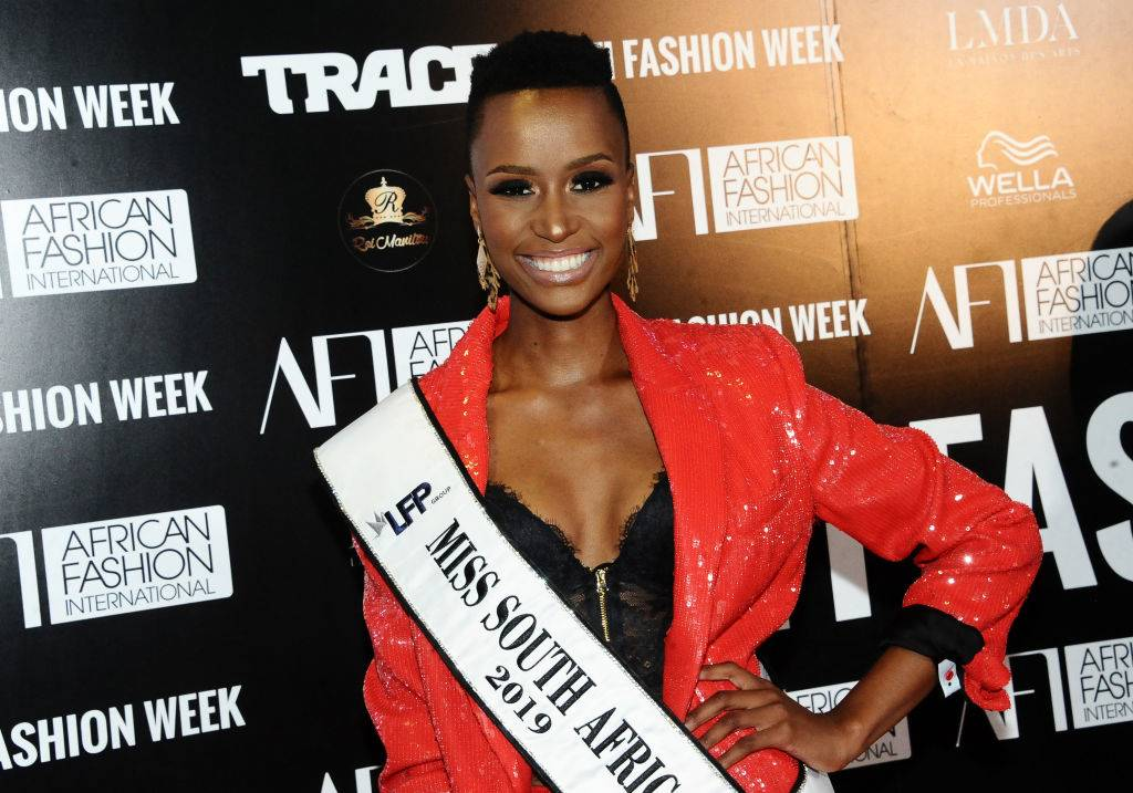 zozibini tunzi wearing her miss south africa sash with a red jacket