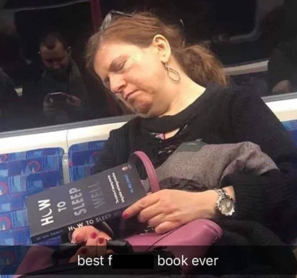woman sleeping on bus holding book titled