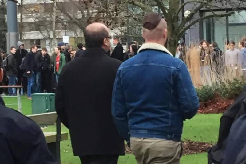 man with head shaved on sides next to man with hair only on sides