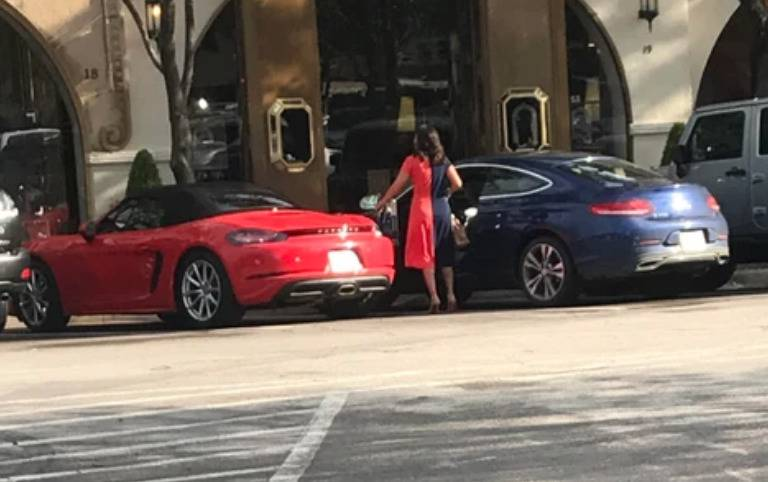 woman with half red, half blue dress standing between two cars of the same shades