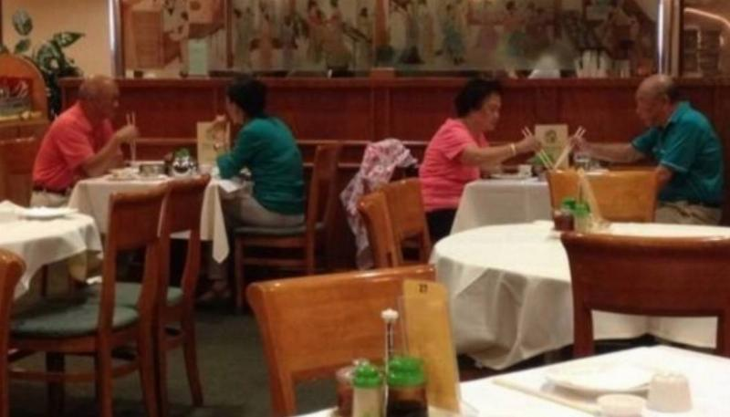 two separate couples at restaurant are wearing matching outfits