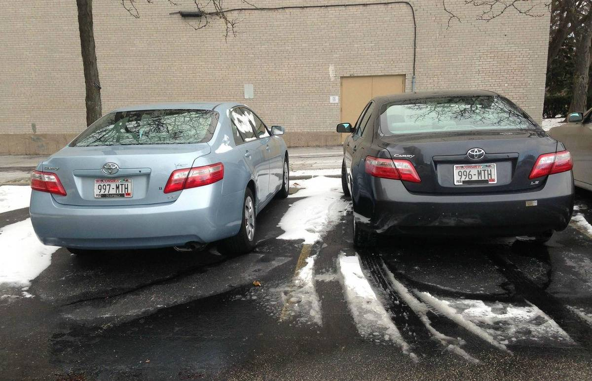 two cars of the same model parked next to each other have nearly identical license plates (one number difference)