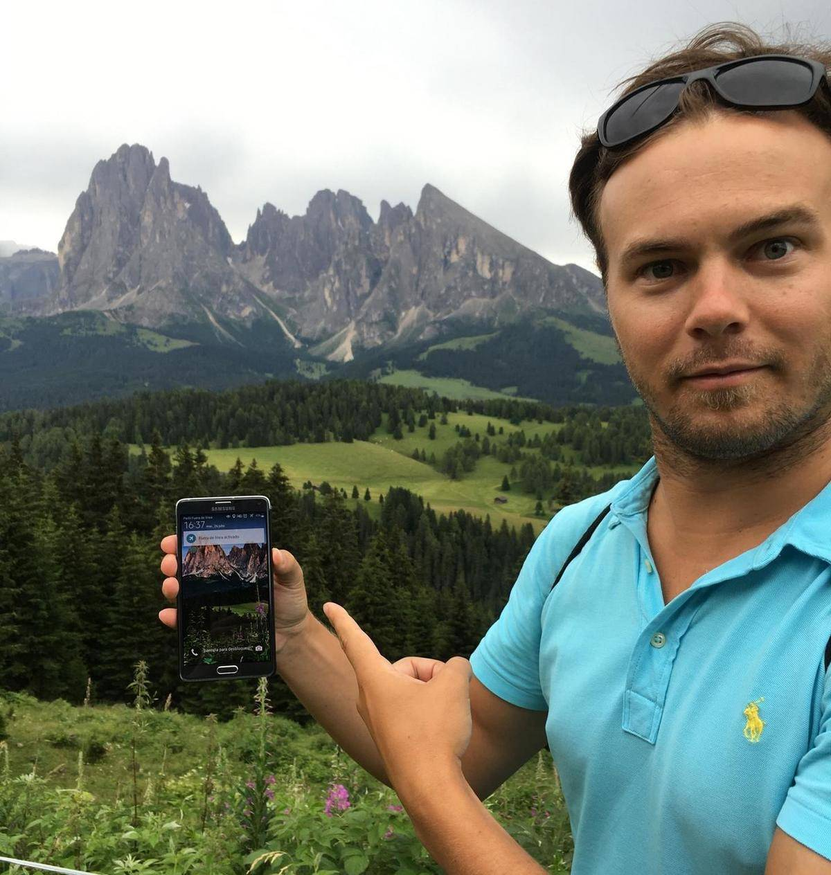 man holding phone of picture of mountains in front of the mountains in real life