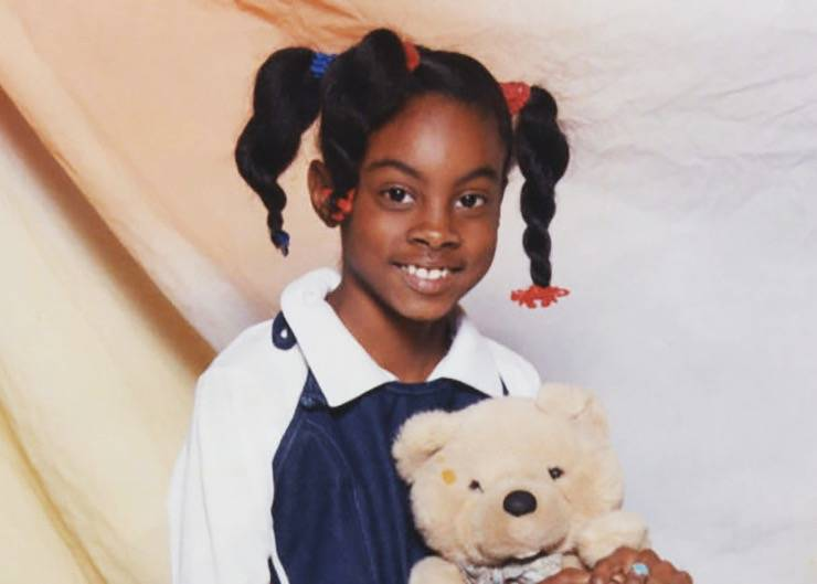 A portrait shows nine-year-old Asha Degree holding a teddy bear.