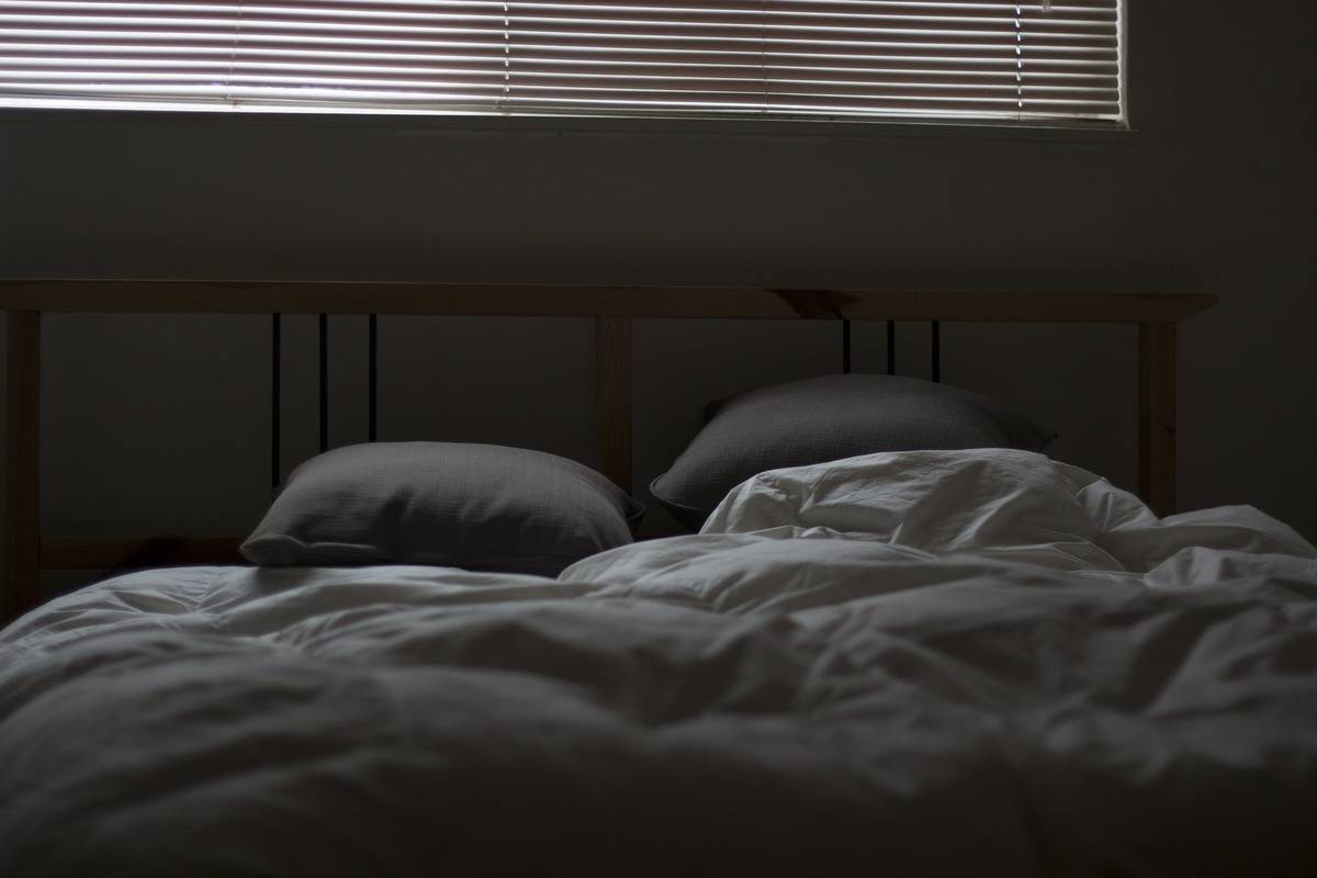 An empty bed with ruffled sheets is seen in the dark.