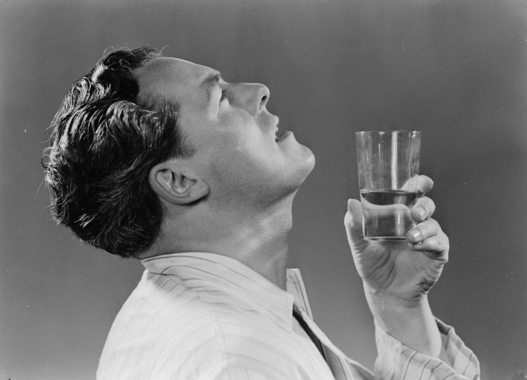 A photograph of a man gargling with a glass of water
