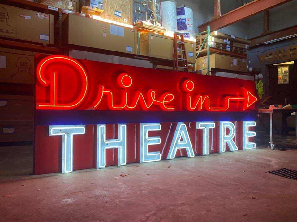 a neon sign that reads drive in theatre