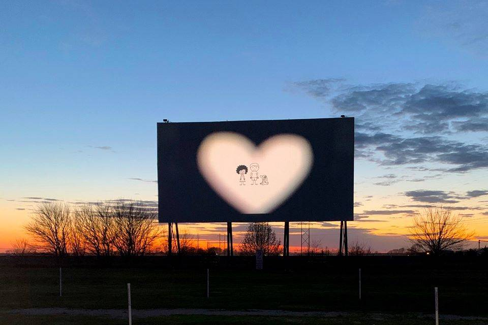 a drive-in at sunset with a heart on screen