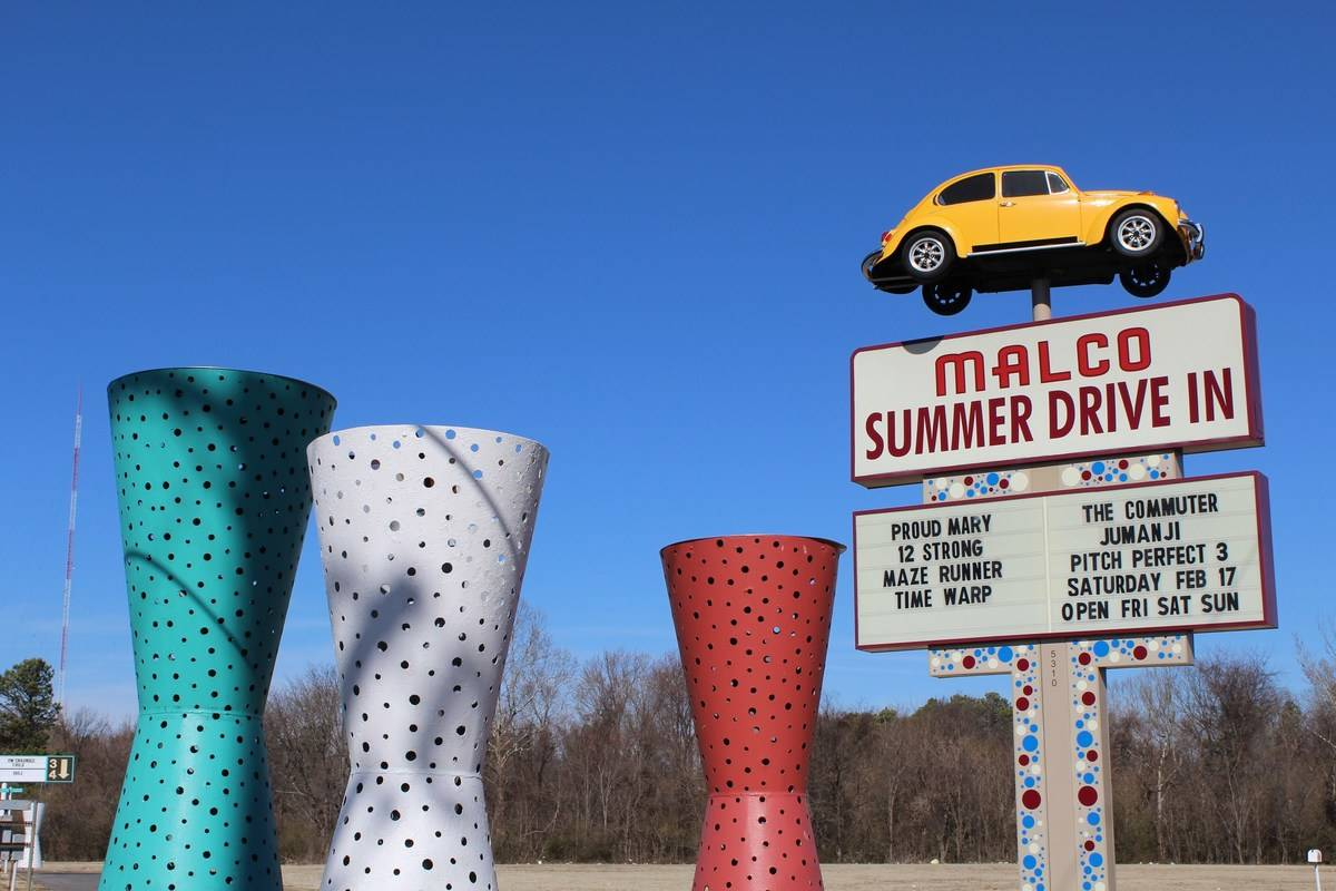 a malco summer drive in sign with a yellow car and colorful sculptures