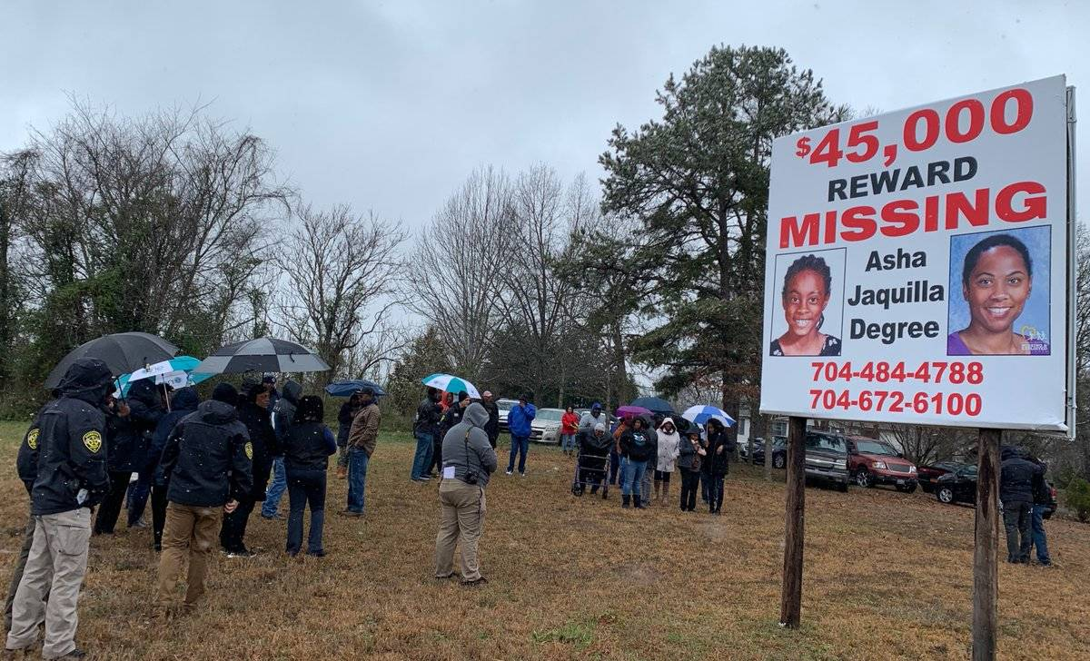 People gather around a missing person's billboard of Asha Degree.