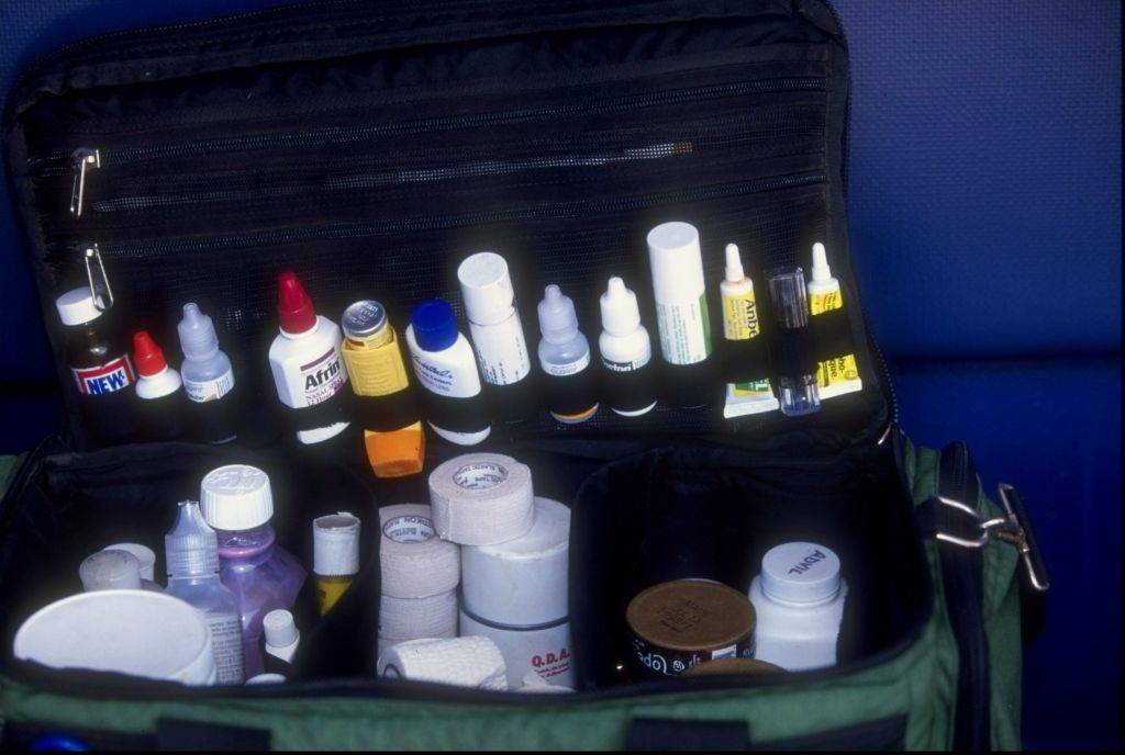 the inside of a first aid kit with bandages, lotions, and other medicine