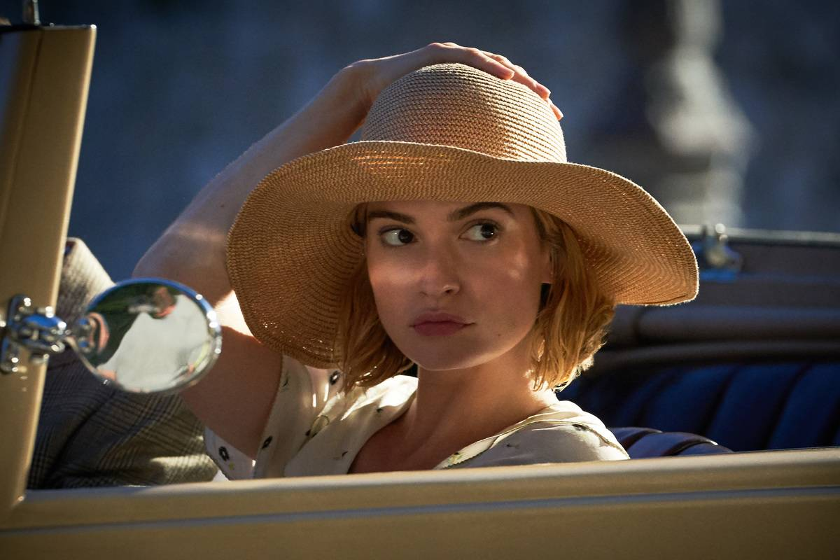 lily james sitting in a car wearing a hat in rebecca