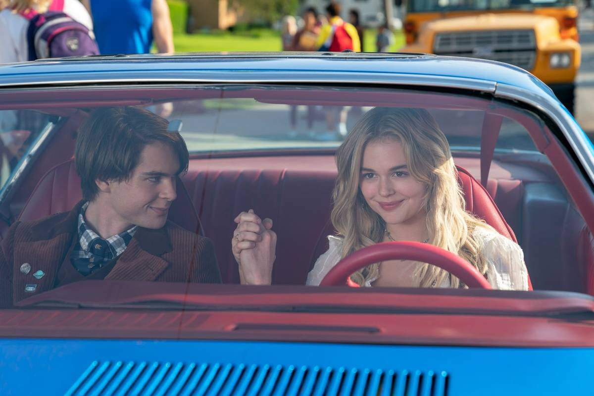 two teenagers holding hands inside a car in the babysitter killer queen