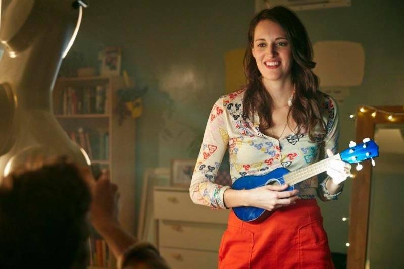 a woman holding a blue ukulele crashing