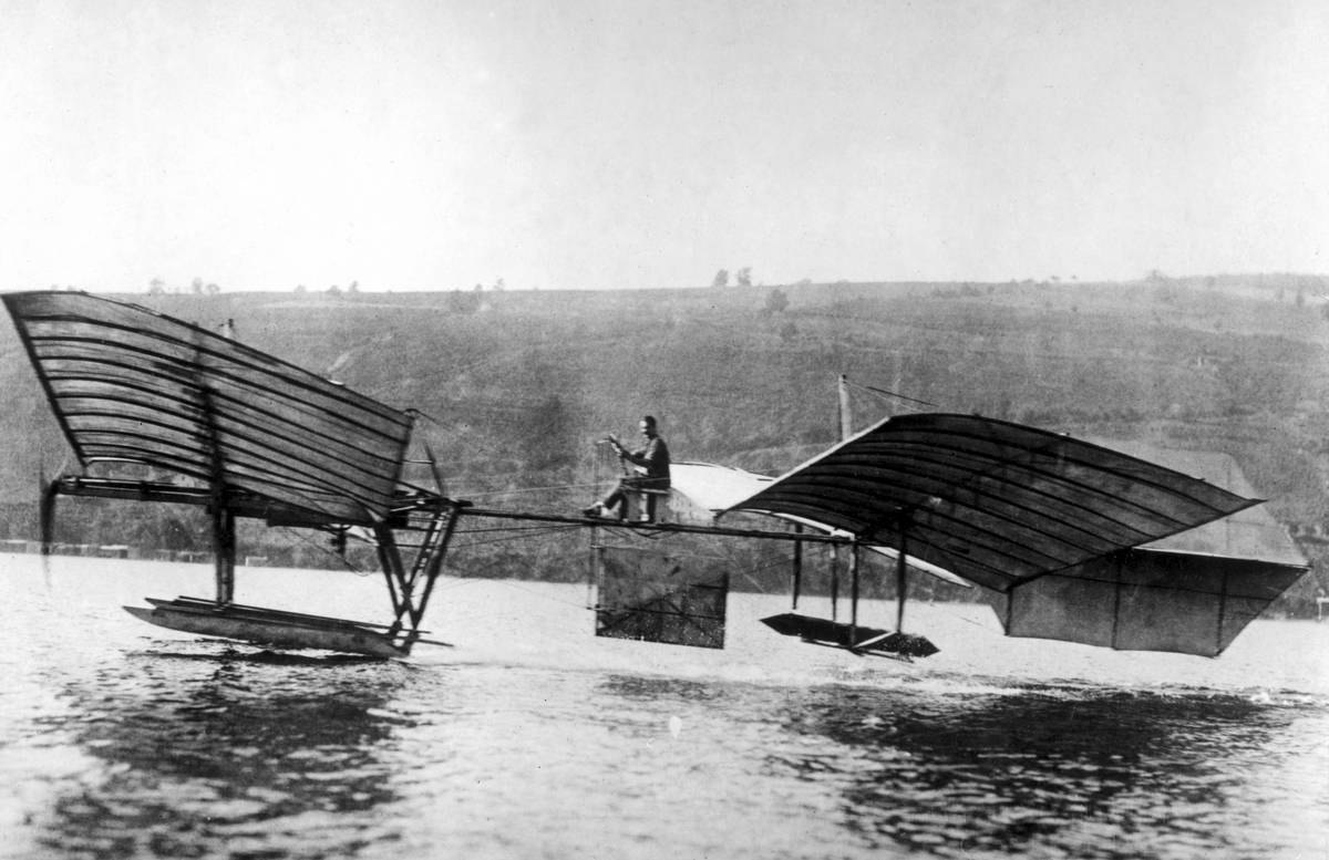 Glenn Curtiss flyies the modified Langley 'aerodrome' above the water.