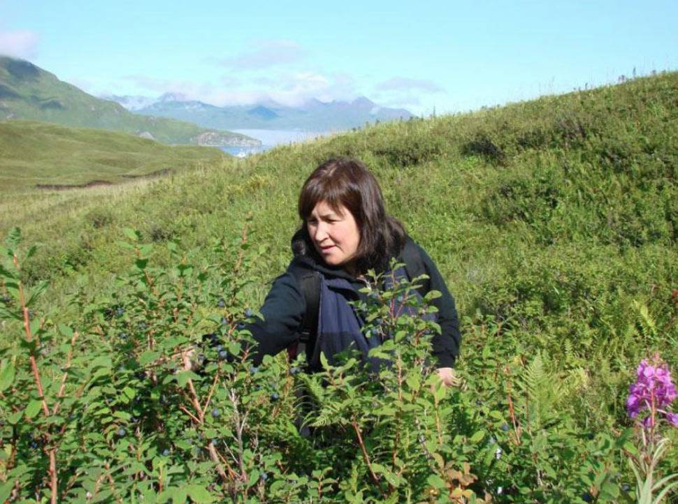 Pam Aus sits in a flower field.