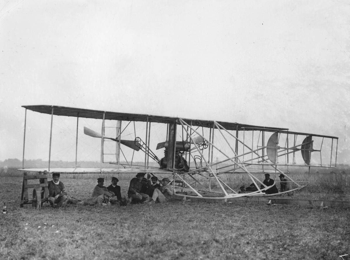 A group of men shelter under Eugene Lefebvre's Wright Type A Flyer.
