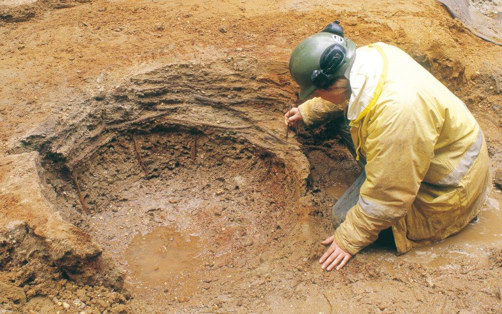 An archaeologist carefully excavating a construction pit