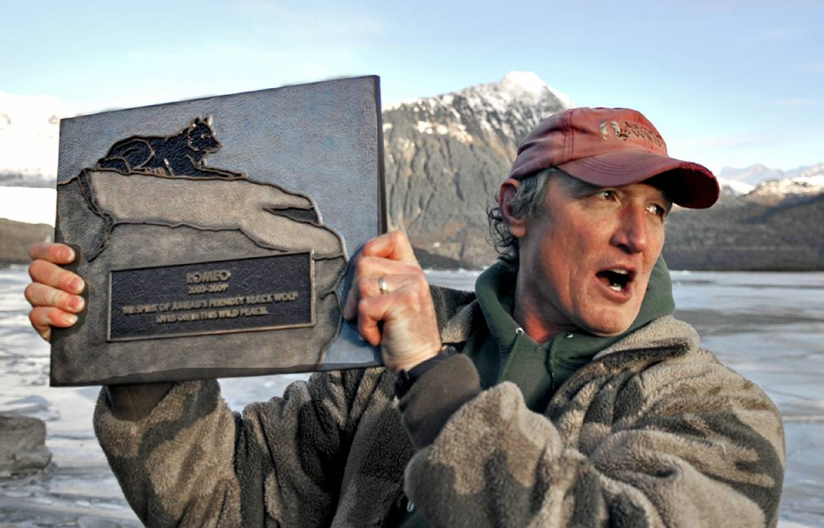 Author Nick Jans holds up a plaque made for Romeo the wolf.