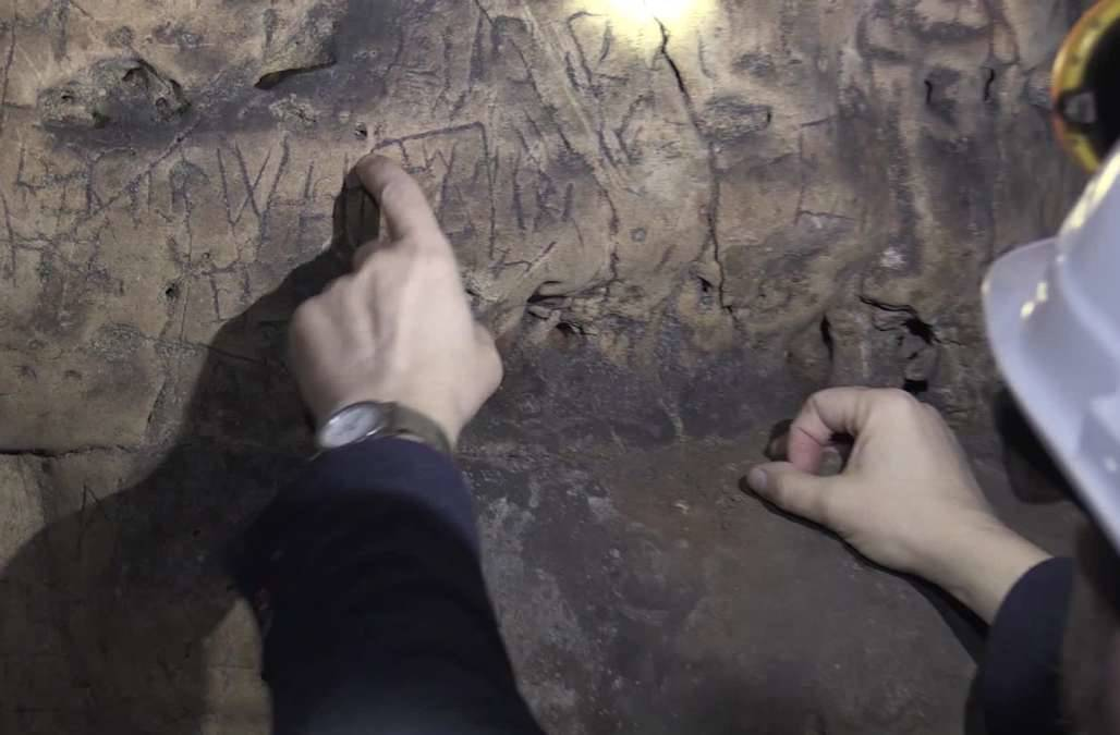 a person pointing to markings on the dirt walls