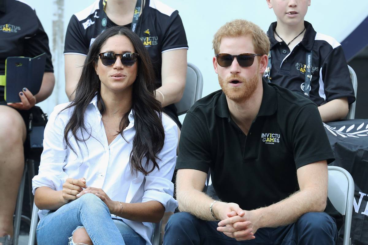 Meghan Markle watches the Invictus Games while wearing a white collared shirt and jeans.