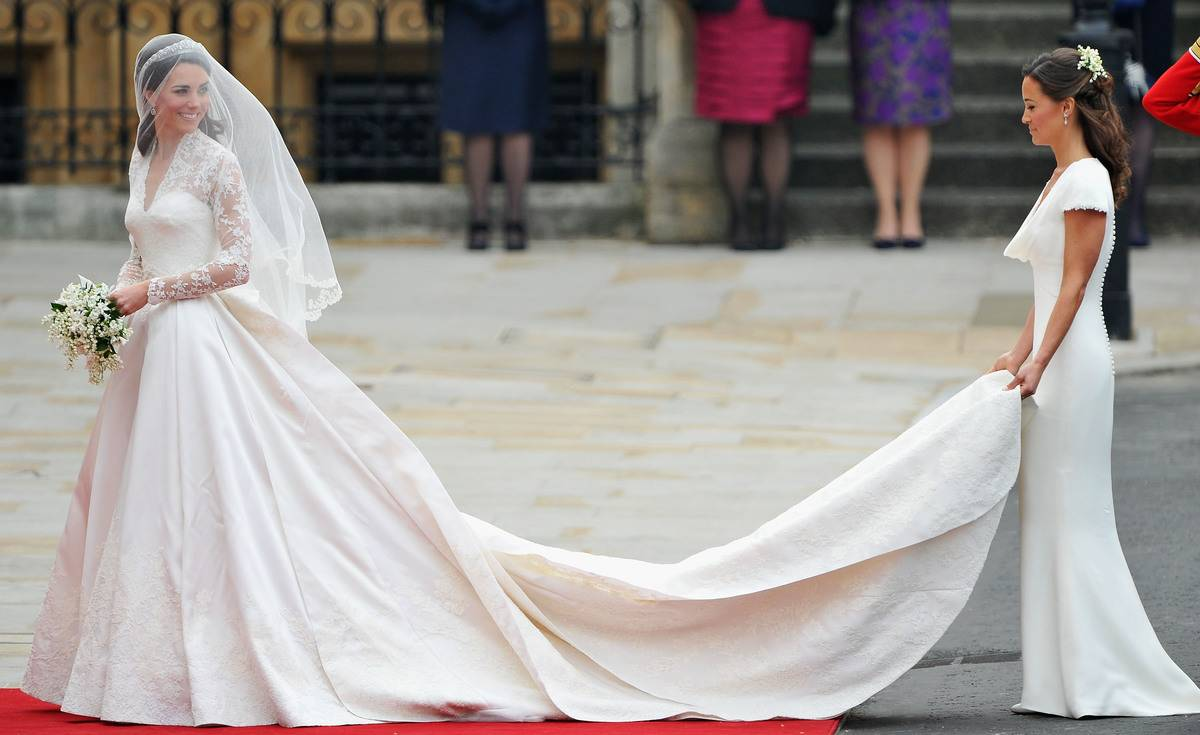 Kate Middleton walks toward her wedding as her sister spreads out her wedding dress.